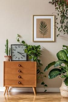 デザインヴィンテージの椅子とcommode、植物、サボテン、時計、パーソナルアクセサリー、ベージュの壁にゴールドのモックアップポスターフレームを備えたリビングルームのレトロなインテリアデザイン。スタイリッシュな家の装飾。レンプレート。