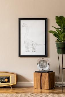 緑の鍋、ヴィンテージラジオ、木製の立方体、ランプ、ベージュの壁に黒のモックアップ額縁の植物とリビングルームのレトロなインテリアデザイン。家の装飾のミニマルなコンセプト。テンプレート。