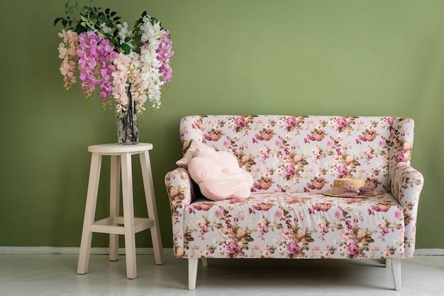 レトロなインテリア。古いヴィンテージのレトロなインテリアの木製の床に花のソファと花瓶と緑の壁