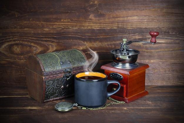 레트로 보석 상자, 커피와 증기가있는 검은 색 머그잔, 체인이 달린 회중 시계, 갈색 나무 판자 배경에 손잡이가있는 빈티지 커피 분쇄기.