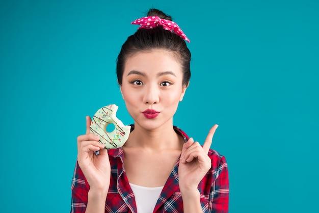 レトロな楽しい女性は、青い背景の上に立っているお菓子、デザートをお楽しみください。