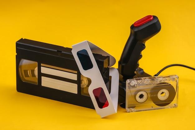 노란색 배경에 3d 안경, 오디오 및 비디오 카세트가 있는 레트로 조이스틱. 속성 80년대