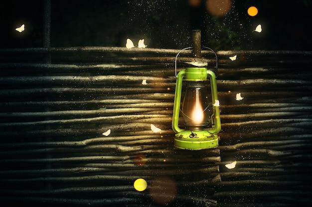 Retro kerosene lamp with luminous moths in the dark