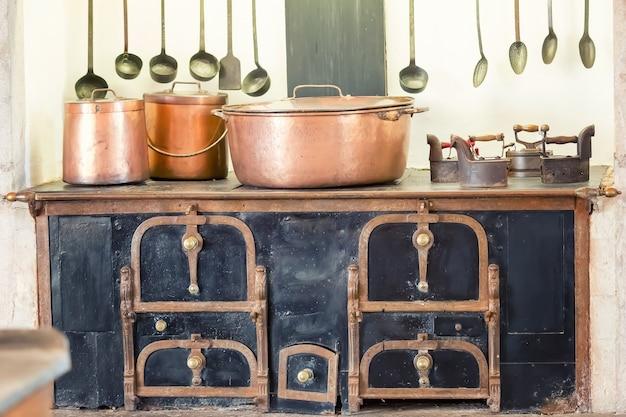 Ретро интерьер кухни со старыми сковородками, горшок на печи