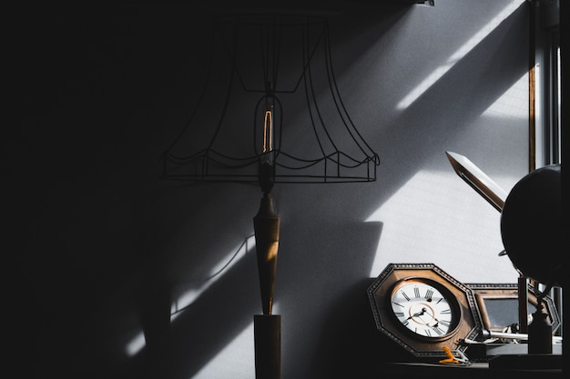 Retro lamp, clock and stuff in living room against sun light and shadow from window