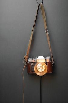 灰色の背景にエジソンランプ付きの古いカメラからのレトロなランプ。コンセプトは良い考えです。