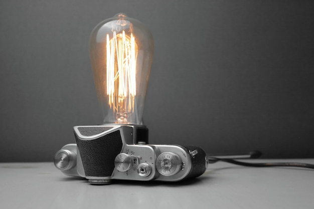 Ретро лампа из старого фотоаппарата с лампой эдисона на сером