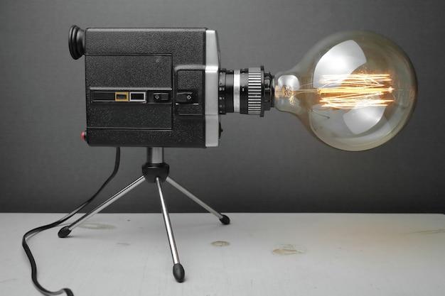 회색에 에디슨 램프와 함께 오래 된 카메라에서 레트로 램프