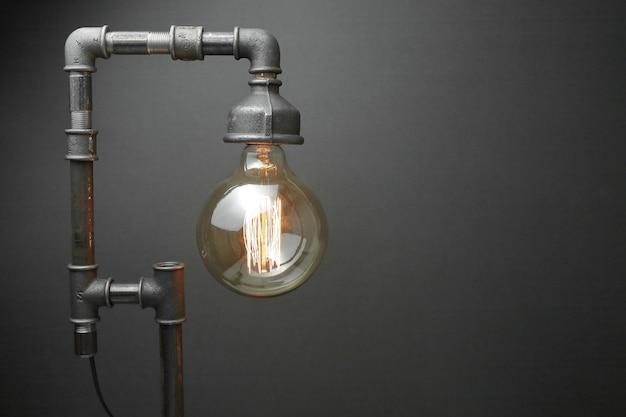 灰色の背景にエジソンランプと金属製の水道管で作られたレトロなランプ。コンセプトは良い考えです。