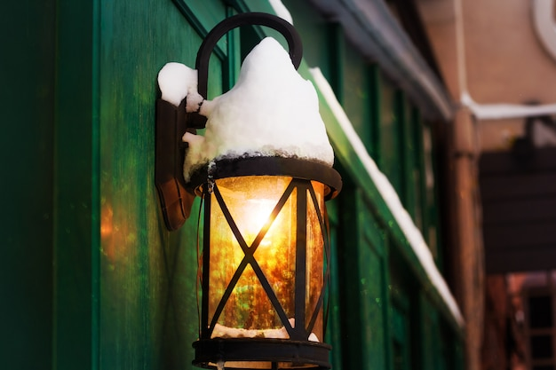 Retro lantern covered with snow with shining light and bokeh