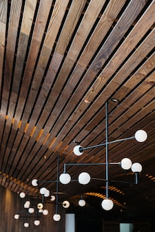 Retro light bulb lamps hang from dark oak wooden ceiling. warm, cozy and elegant design.