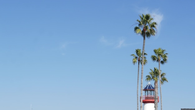 복고풍 등대, 열대 야자수와 푸른 하늘. 빨간색과 흰색 빈티지 구식 신호입니다. 바다 항구 근처 해안가 어부 마을. 부두 또는 항구, 미국 캘리포니아의 화창한 여름.