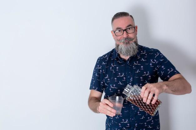 大きなあごひげと眼鏡をかけたレトロな外観のヒップスター4045歳の白人が古い酒瓶を持ってまっすぐ前を見ている