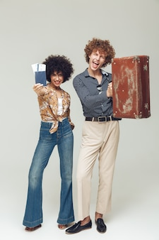 Retro loving couple holding suitcase passport and tickets.