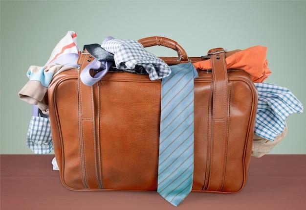 背景にカラフルな服とレトロな荷物