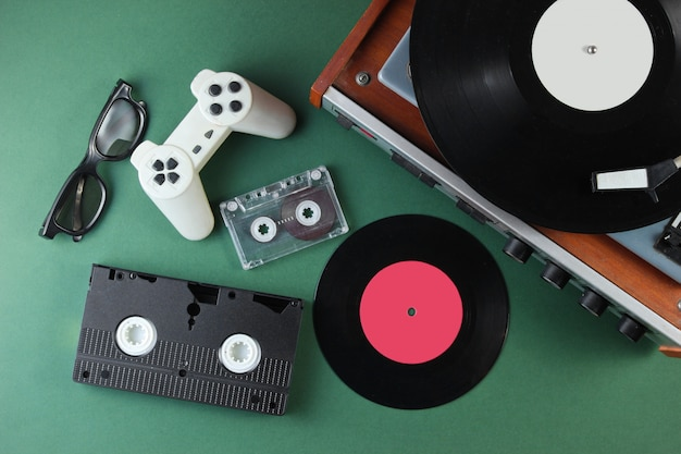 Ретро медиа и развлекательные товары 80-х годов. виниловый проигрыватель, видео, аудиокассеты, 3d очки, геймпад на зеленой поверхности.
