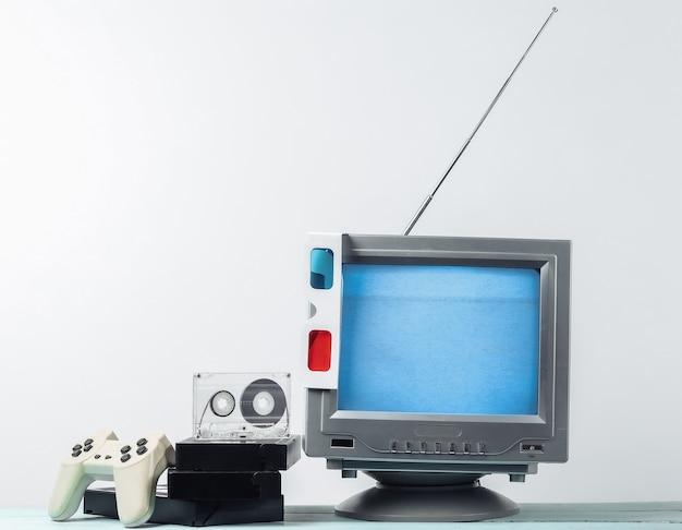 80 年代のレトロなメディア、エンターテイメント。昔ながらのレトロなテレビ受信機、アナグリフ ステレオ グラス、オーディオとビデオのカセット、白い壁にゲームパッド。