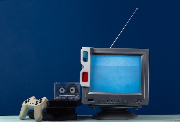 Retro media, entertainment 80s. antenna old-fashioned retro tv receiver, anaglyph stereo glasses, audio and video cassette, gamepad on classic blue.