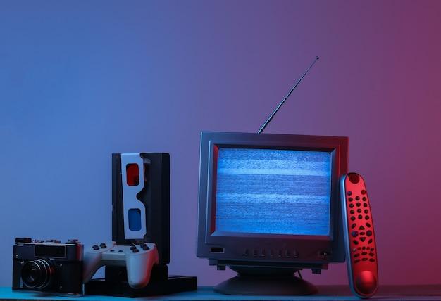 레트로 미디어 엔터테인먼트 80 년대 안테나 구식 tv 수신기 입체 안경 시계 오디오 및 비디오 카세트 게임 패드 카메라 원격 핑크 블루 그라데이션 네온 불빛 레트로 웨이브