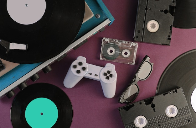 Retro media and entertainment items 80s. vinyl player, video, audio cassettes, 3d glasses, gamepad on red.