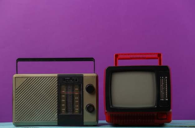 레트로 미디어. 오래 된 휴대용 tv, 보라색 배경에 라디오 수신기
