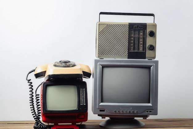 레트로 미디어. 흰색 바탕에 오래된 휴대용 tv, 회전식 전화기, 라디오 수신기