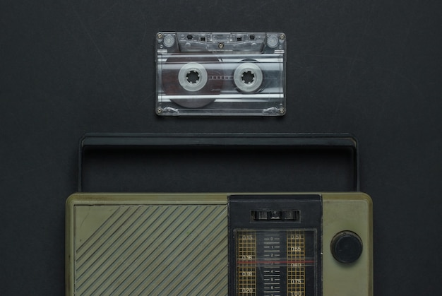 Retro media. radio receiver, audio cassette on black background. top view.