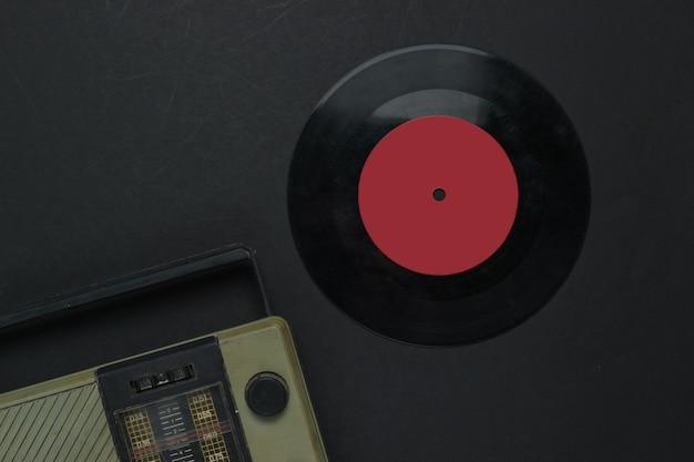 레트로 미디어. 라디오 수신기, 검정색 배경에 비닐 레코드. 평면도.