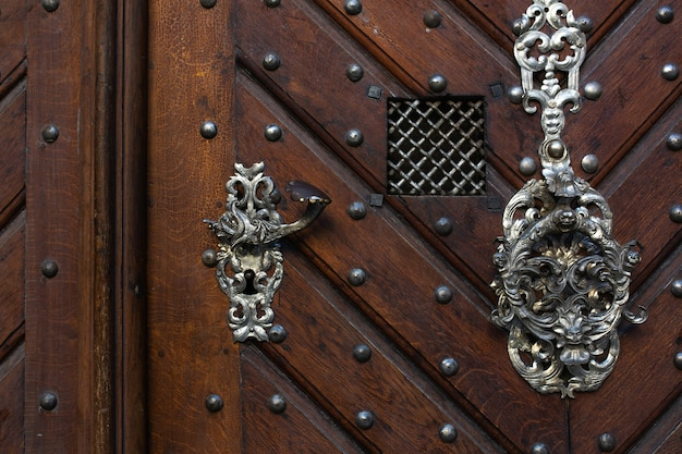 茶色の木製ドアのレトロな金属製のドアハンドル。テキスト用のスペース