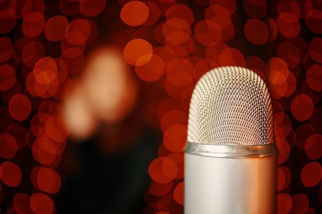 Ретро микрофон на сцене и силуэт женщины в черном платье на светлом фоне боке крупным планом с ...