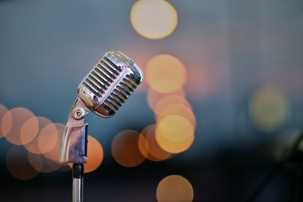 Retro microphone on stage over blurred bokeh background.