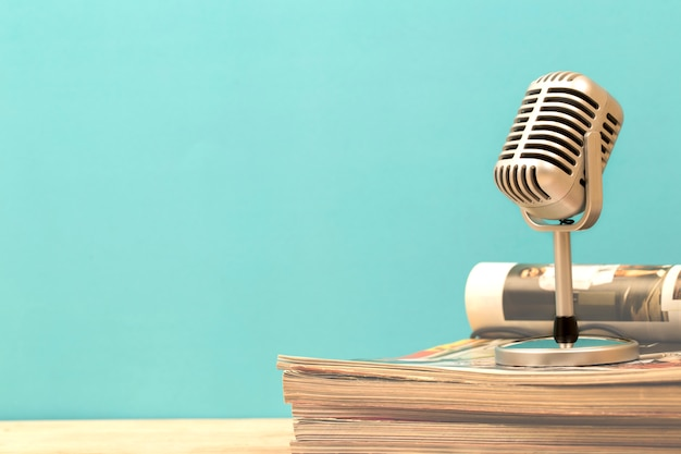Retro microphone with old magazine on wooden table