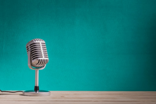 Retro microphone on wooden table with green wall background