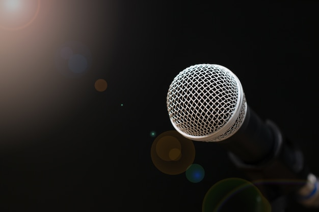Retro microphones with lens light flare on front stage in pub bar or restaurant on black
