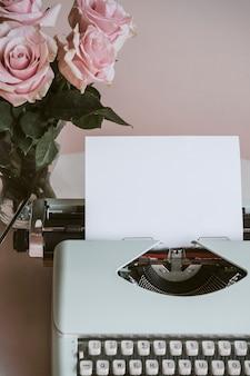 ピンクのバラによるレトロなミントタイプライター