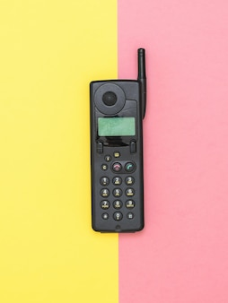 노란색과 분홍색 표면에 안테나와 레트로 휴대 전화