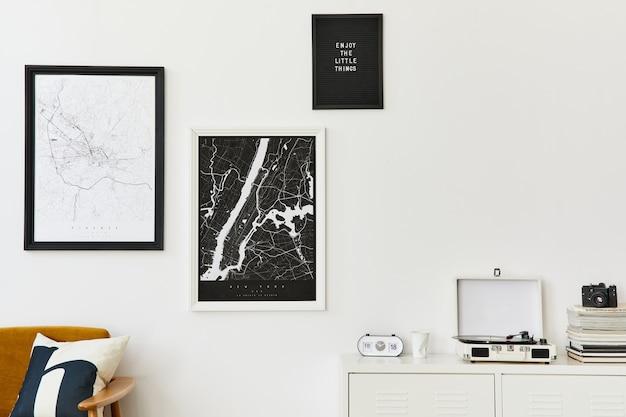 디자인 안락의자, 2개의 모의 포스터 지도, 시계, 식물, 장식, 흰색 벽 및 개인 액세서리가 있는 거실 인테리어의 복고풍 현대적인 구성. 주형.