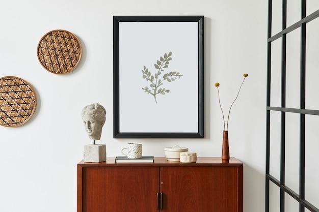 Современная ретро-композиция интерьера гостиной с дизайнерским комодом из тикового дерева, черной рамкой для плаката, книгой, сушеным цветком в вазе, украшением из ротанга, белой стеной и личными аксессуарами. шаблон.
