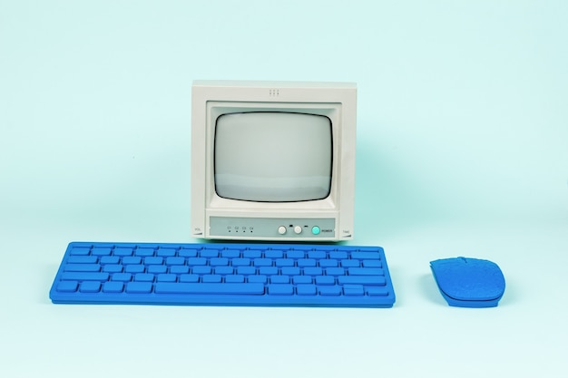 Retro monitor and blue keyboard with mouse on a light background.