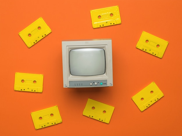 Retro monitor and yellow tape cassettes on an orange background. vintage equipment. flat lay.