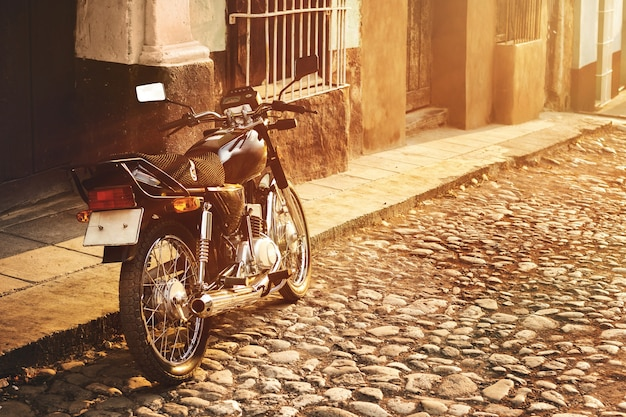 Retro motorcycle on the old city street with cobbled road