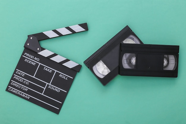 Доска с хлопушкой ретро кино и видеокассета на голубой пастельной предпосылке. кинопроизводство, кинопроизводство. 80-е гг. вид сверху