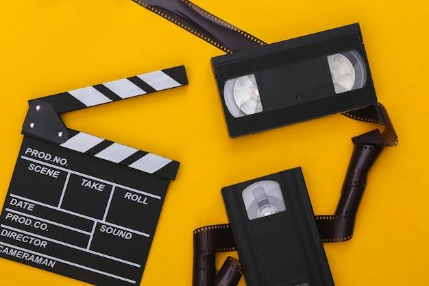 노란색 배경에 레트로 영화 클래퍼 보드, 비디오 카세트 및 필름 테이프. 영화제작, 영화제작. 80년대. 평면도