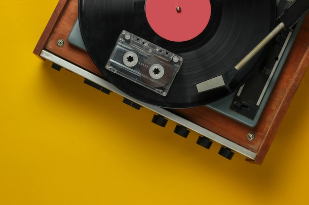 Retro music concept. vinyl record player with a vinyl record, audio cassette on yellow background. 80s. top view