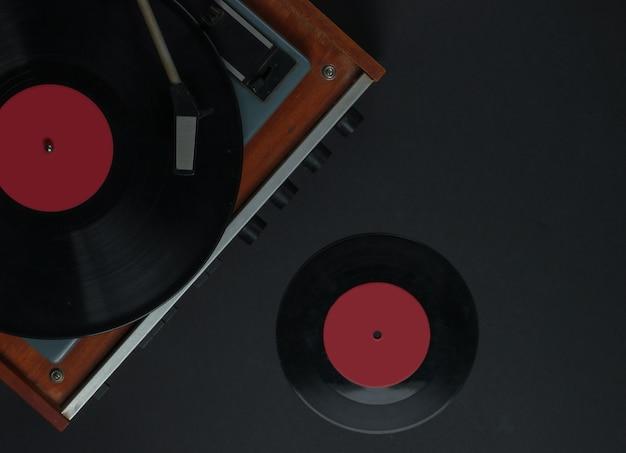 레트로 음악 플레이어. 검정색 배경에 비닐 레코드와 비닐 레코드 플레이어. 70 년대. 평면도