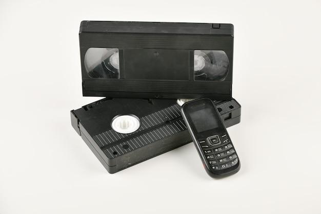 白い背景の上のレトロなオブジェクト。押しボタン式電話とビデオカセット。過去のアナログメディア技術。コピースペース