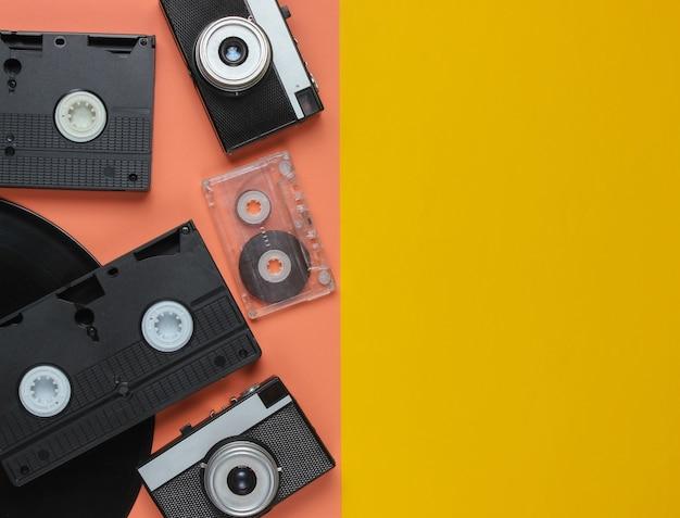 Ретро объекты. ретро фотоаппарат, виниловая пластинка, видеокассеты, аудиокассеты на цветном фоне с копией пространства.