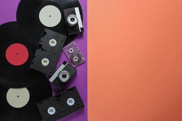 Ретро объекты. ретро фотоаппарат, виниловые пластинки, видеокассеты, аудиокассеты на цветном фоне с копией пространства.