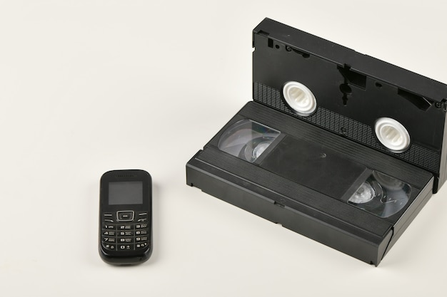 Retro objects on a white background. push-button telephone and video cassette. analog media technology of the past. copy space