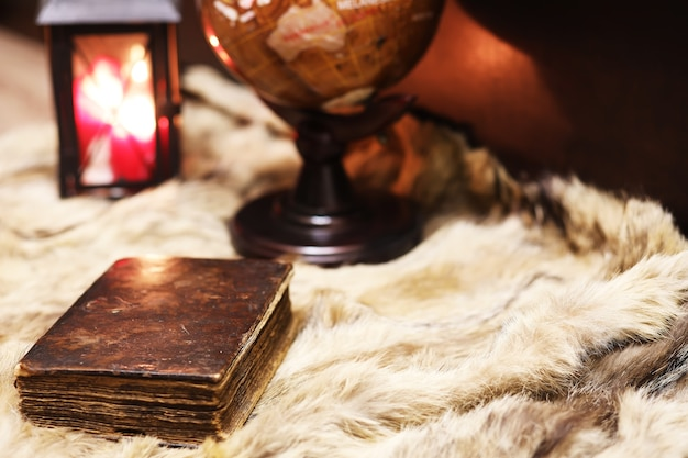 Retro old book and world desk globe on fur, learning and education concepts.